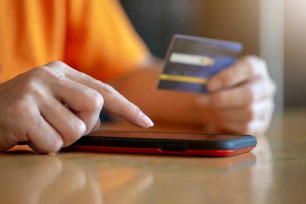 Compras on-line pagamento com cartão de crédito, o homem usando smartphone móvel, comércio eletrônico e conceito de aplicação Foto Premium