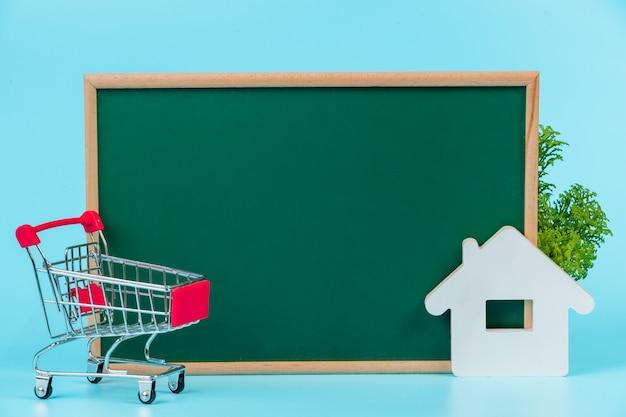 Compras on-line, um carrinho duplo colocado em uma placa verde em um azul. Foto gratuita