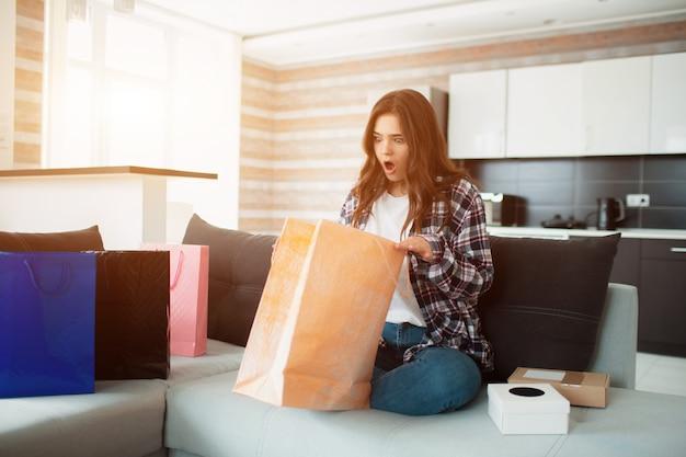 Compras on-line, uma jovem mulher ordenou entrega em domicílio. agora ela se senta no sofá e desembala suas novas compras. Foto Premium