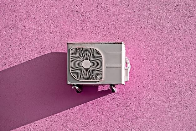 Compressor de ar condicionado moderno na parede grunge rosa com sombra Foto Premium