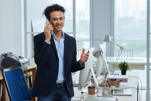 Comprimento médio do empresário asiático falando ao telefone em seu escritório de luz Foto gratuita