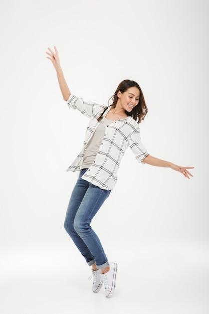 Comprimento total alegre mulher morena de camisa dançando sobre cinza Foto gratuita