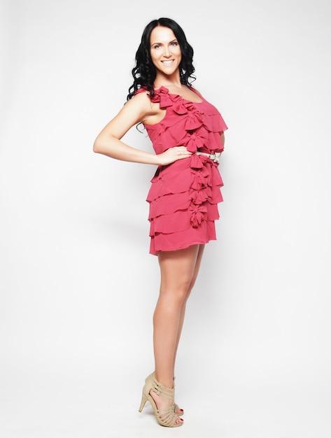 Comprimento total da morena feminina com vestido rosa posando, estúdio tiro Foto Premium
