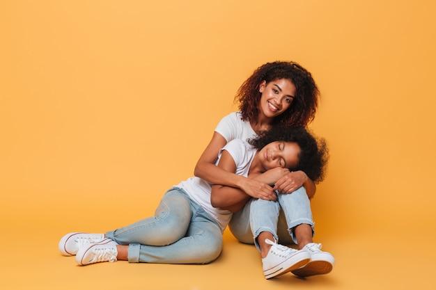 Comprimento total de duas adoráveis irmãs africanas Foto gratuita