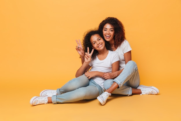 Comprimento total de duas irmãs africanas felizes Foto gratuita