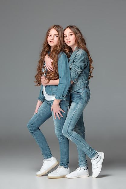 Comprimento total de jovem magro feminino em jeans na parede cinza Foto gratuita