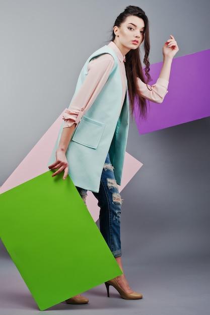 Comprimento total de menina bonita, com placa de publicidade em branco verde, sobre fundo cinza e banner rosa e violeta Foto Premium