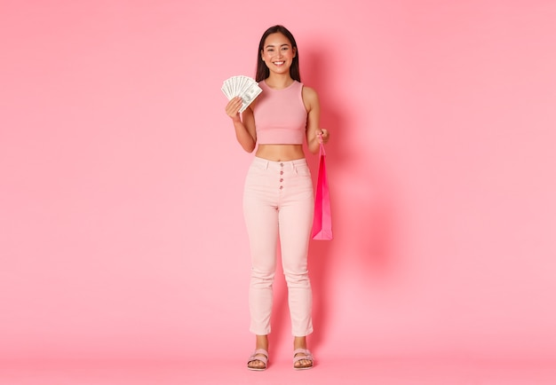 Comprimento total de uma atraente garota asiática sorridente com roupas de verão, segurando dinheiro e sacola de compras, comprando algo caro, curtindo um passeio em shoppings, em pé na parede rosa Foto gratuita