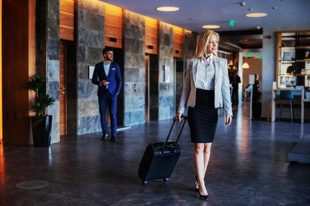 Comprimento total de uma loira de meia-idade com roupa formal, caminhando no saguão de um hotel chique e puxando a mala. ela escapou dos problemas diários. Foto Premium