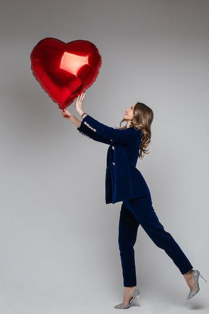 Comprimento total de uma mulher atraente em um terno de veludo azul com jaqueta e calças Foto gratuita