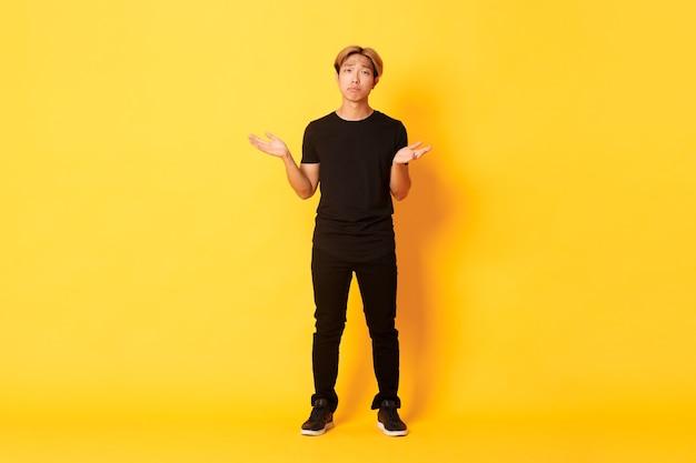 Comprimento total do cara asiático decepcionado e frustrado, encolhendo os ombros, parecendo uma parede amarela triste. Foto gratuita