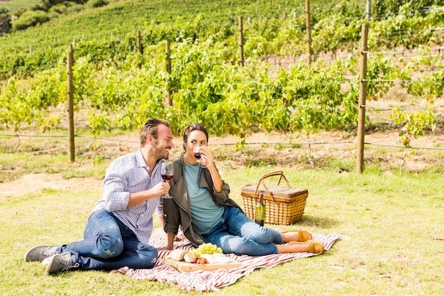 Comprimento total do casal tomando vinho na vinha Foto Premium