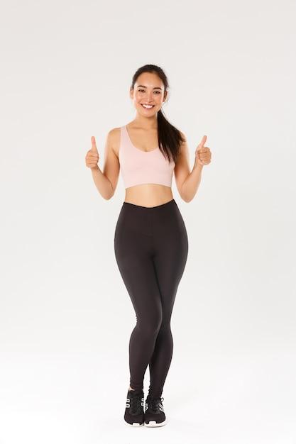 Comprimento total do sorriso satisfeito, menina asiática bonita fitness, desportista em roupa ativa mostrando o polegar para cima e sorrindo satisfeita, orgulhosa feminina athelte ganhar objetivo de treino diário, fundo branco. Foto Premium