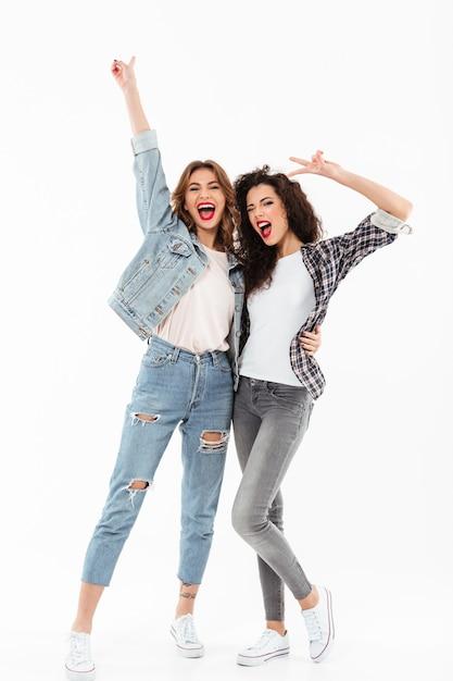 Comprimento total duas meninas alegres juntos e mostrando gestos de paz sobre parede branca Foto gratuita