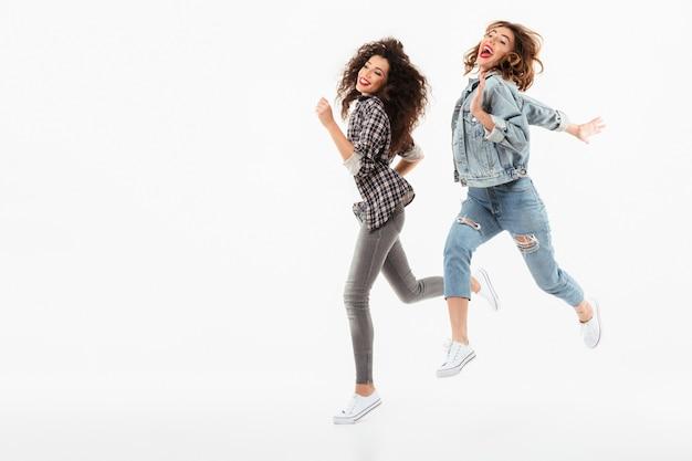 Comprimento total, duas meninas brincalhão correndo juntos sobre parede branca Foto gratuita