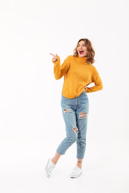 Comprimento total mulher alegre na camisola posando com o braço no quadril hile apontando e olhando para longe sobre parede branca Foto gratuita