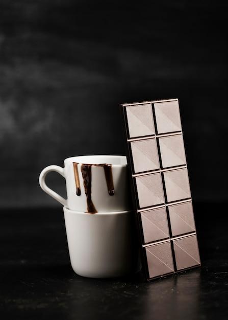 Comprimido de chocolate e chocolate derretido em canecas Foto gratuita