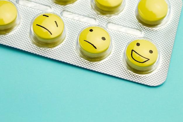 Comprimidos amarelos e caretas em uma bolha. o conceito de antidepressivos e cura Foto Premium