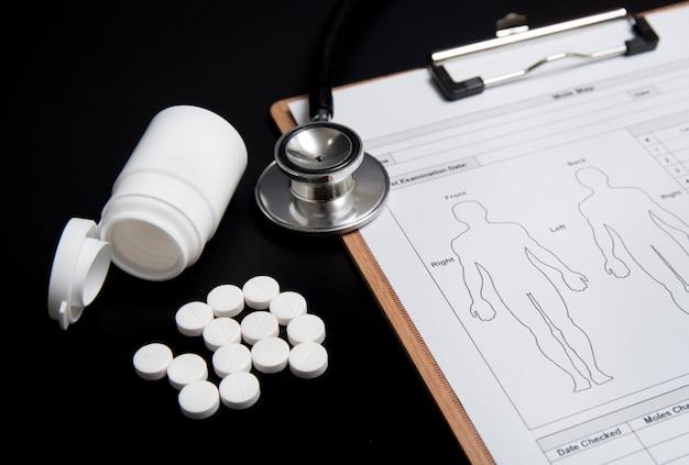 Comprimidos brancos e um frasco branco, juntamente com um estetoscópio e uma ficha médica, estão sobre um preto. Foto Premium