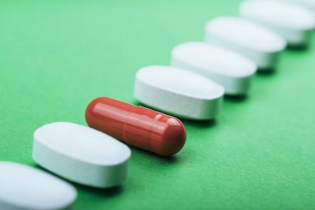 Comprimidos brancos médicos e cápsulas marrons para o tratamento e cuidados de saúde em um fundo verde Foto Premium