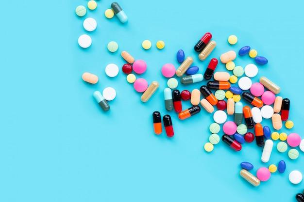 Comprimidos coloridos com cápsulas e comprimidos em azul Foto Premium