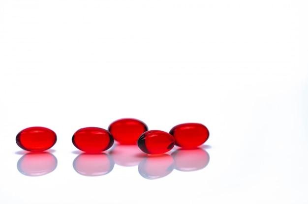 Comprimidos de cápsula de gel macio vermelho isolados. pilha de cápsula de gelatina macia vermelha. vitaminas e conceito de suplementos alimentares. indústria farmacêutica. farmácia farmácia. Foto Premium
