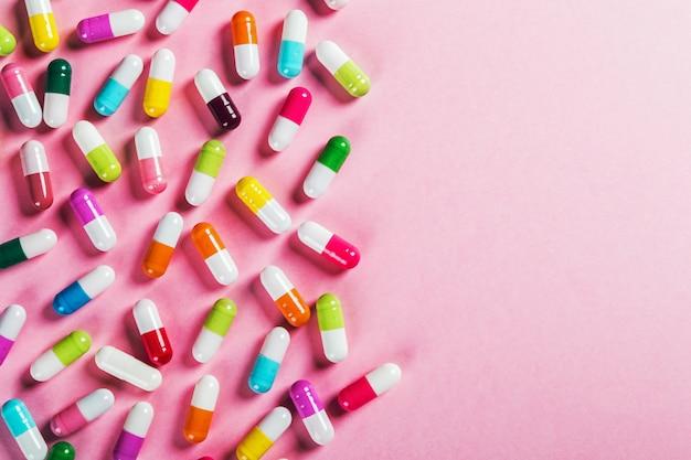 Comprimidos de cores diferentes em fundo rosa Foto Premium