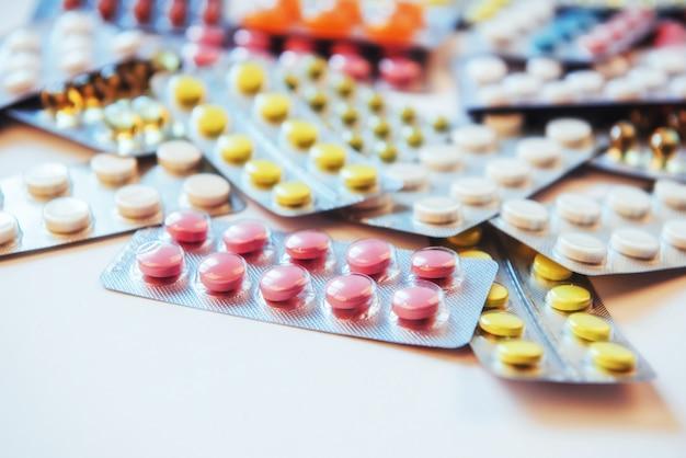 Comprimidos de cores diferentes estão na superfície em uma embalagem selada Foto Premium