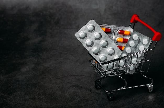 Comprimidos e carrinho de compras no conceito de economia de fundo escuro. saúde e medicina Foto Premium