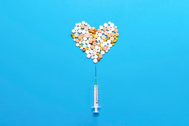 Comprimidos em forma de um coração e uma seringa presa sobre um fundo azul. conceito da indústria farmacêutica, medicina, tratamento e recuperação após doenças cardiovasculares. vista plana, vista superior Foto Premium