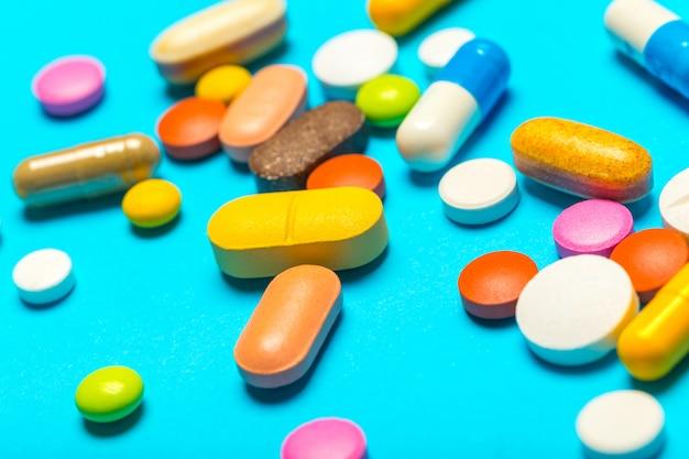 Comprimidos estão espalhados sobre um fundo azul Foto Premium