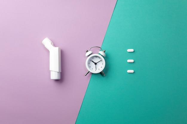 Comprimidos, inalador e despertador branco sobre fundo colorido. conceito de medicina e saúde em estilo minimalista Foto Premium