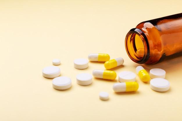 Comprimidos multicoloridos e cápsulas de comprimidos de garrafa de vidro amarelo Foto Premium