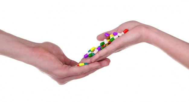 Comprimidos na mão, isolado no fundo branco Foto Premium