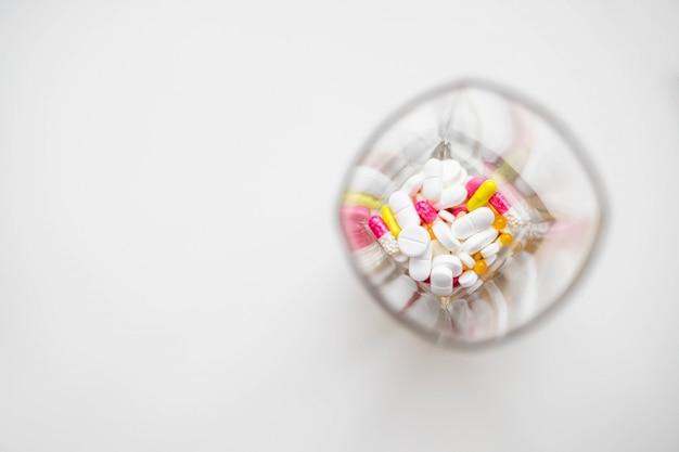 Comprimidos ou cápsulas de medicamento em vidro em fundo branco. prescrição de medicamentos para medicação de tratamento. medicamento farmacêutico. Foto Premium