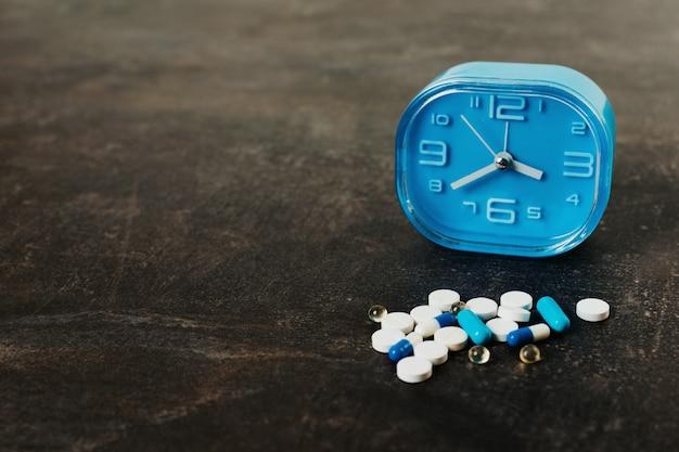 Comprimidos variados e relógio azul na mesa escura. conceito de medicamento saudável Foto Premium