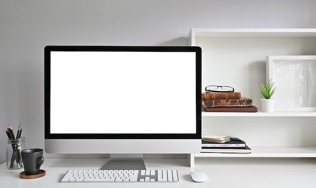 Computador de maquete do espaço de trabalho na mesa de escritório e livros, moldura e livros nas prateleiras. Foto Premium