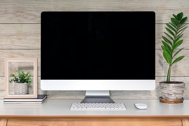 Computador desktop de maquete com tela preta na mesa de madeira. Foto Premium