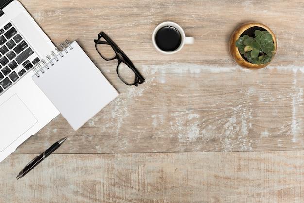 Computador portátil; bloco de notas em espiral; óculos; chá preto e planta na mesa de madeira Foto gratuita
