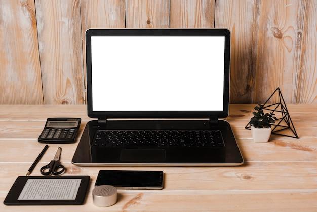 Computador portátil; calculadora; lápis; tesoura; telefone celular e leitor de ebook na mesa de madeira Foto gratuita