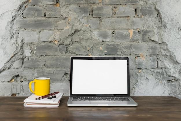 Computador portátil; copo amarelo; e artigos de papelaria na mesa de madeira Foto gratuita