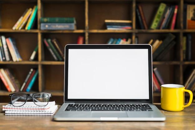 Computador portátil; copo; espetáculos e bloco de notas em espiral na mesa de madeira Foto gratuita