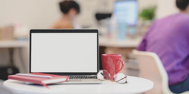 Computador portátil de tela em branco com material de escritório em escritório moderno Foto Premium