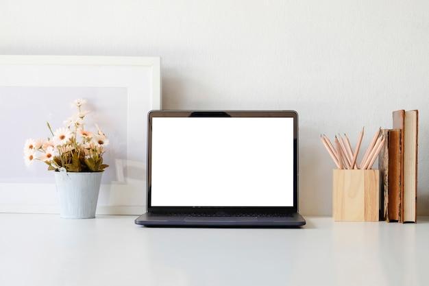 Computador portátil e flor do modelo no espaço de trabalho com copo e livro de café. Foto Premium