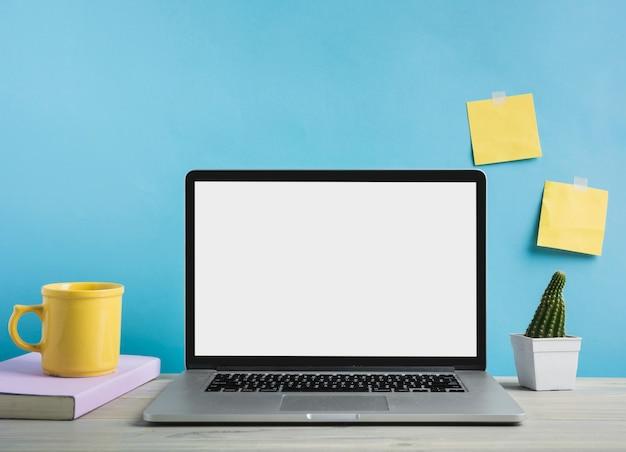 Computador portátil; livro e xícara de café na frente da parede azul Foto gratuita