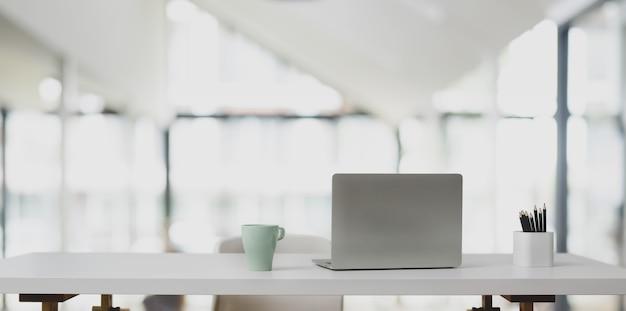 Computador portátil na mesa branca e xícara de café no escritório moderno Foto Premium