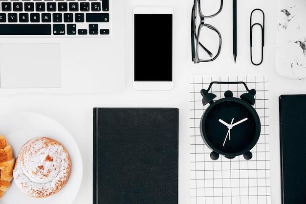 Computador portátil; telemóvel e tablet digital; óculos; lápis; pastelaria assada e página de despertador Foto gratuita