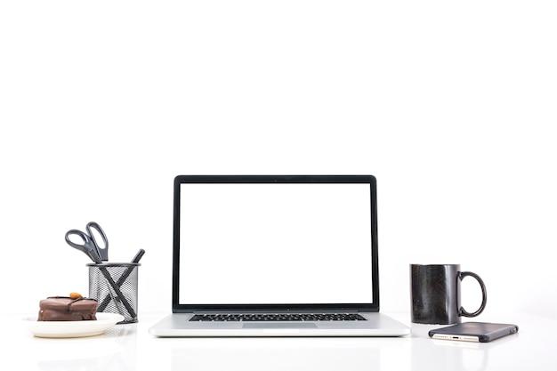 Computador portátil; xícara de café; telefone móvel e bolo no fundo branco Foto gratuita