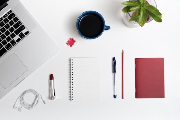 Computador portátil; xícara de chá; fone de ouvido; batom e papelaria do escritório na mesa branca Foto gratuita