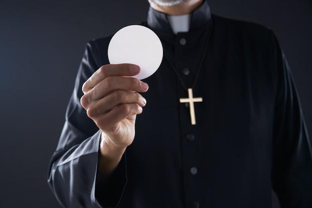 Comunhão wafer hostia padre nas mãos Foto Premium